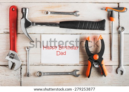 Greeting Card to Happy Birthday Dad, concept, set of different tools: a hammer, wrench, screwdriver, various spanners, clamp and tablet with text \