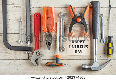 Greeting Card to Happy Father\'s Day, concept, set of different tools: a hammer, Hand saw, pliers, wrench, screwdriver, various spanners, clamp on a wooden background and text , closeup, top view