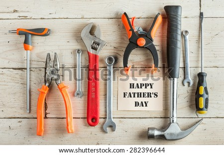 Greeting Card to Happy Father\'s Day, concept, set of different tools: a hammer, pliers, wrench, screwdriver, various spanners, clamp on a wooden background and tablet for  inscription, text, top view
