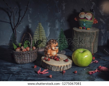 Greeting card. Toys, forest dwellers. The hedgehog crouched on a stump. Near the basket with the collected nuts. An owl is sleeping on a high stump in the background.