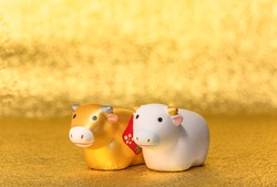 Greeting card with a close-up on two cute hand made figurines of the zodiac animal of two cows hand painted in gold and white for the year of the ox on  an uneven textured golden background.