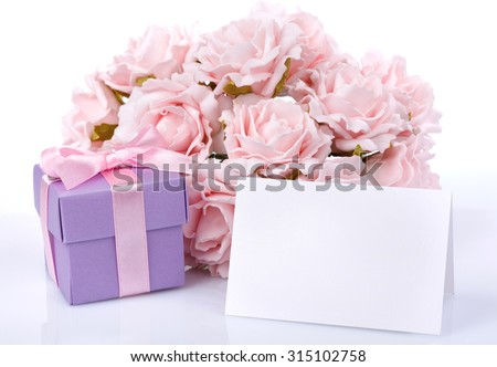 Greeting card with pink flowers and a purple gift box with ribbon and bow on a white background