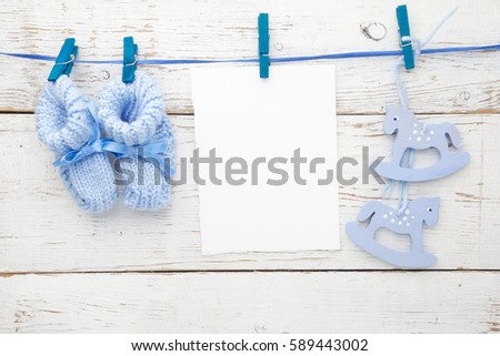 Greeting children form with blue booties and wooden horse. Flat lay