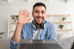 Greeting Concept. Portrait of excited young man waving hello with hand looking at camera, using laptop at home office. Cheerful guy saying hi or goodbye during video call, webcam view