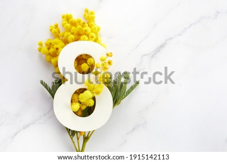 Greeting for International Women's Day on March 8th. Branches of mimosa and number eight.