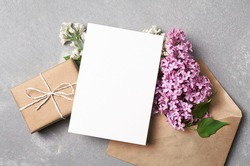Greeting or invitation card mockup with gift box, envelope and spring lilac flowers on grey concrete background, top view, copy space