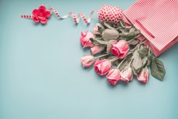Greeting pink pale roses bunch in shopping bag with ribbon on turquoise blue background, top view, copy space. Female holidays layout.
