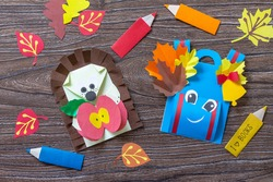Greeting postcard hedgehog with an apple on a wooden table. Handmade. Project of children's creativity, handicrafts, crafts for kids.