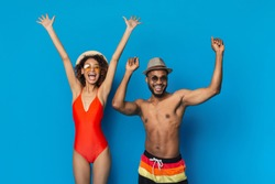 Greeting summer time. Happy african american millennial couple in swimwear jumping on blue studio background