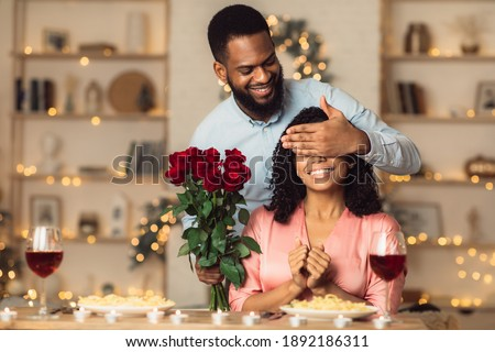 Greeting With Holidays. Smiling black man covering his woman eyes and giving her bunch of red roses, making surprise to beautiful lady. African american couple celebrating together at home or cafe