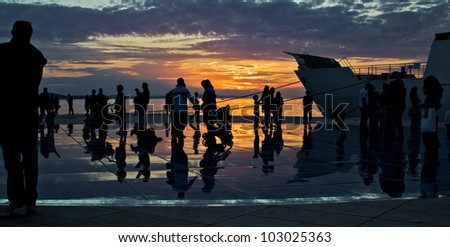 Greetings to the sun installation in Zadar, people silhouette at sunset
