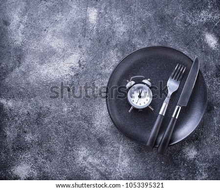 Grey alarm clock in empty plate. Lunchtime concept. Top view