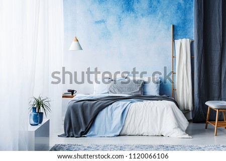 Grey and blue bedding on bed in spacious bedroom interior with ladder and plant