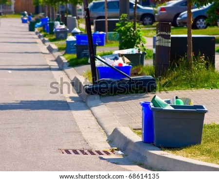 Grey and blue recycling bins by the curb on a residential street.