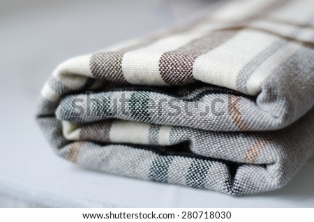 grey and brown checkered knitted folded blanket