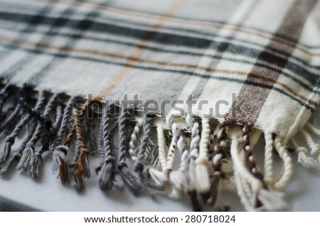 grey and brown checkered knitted folded blanket with fringe