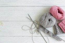 Grey and pink  knitting wool and knitting needles on white wooden background. top view.copy space
