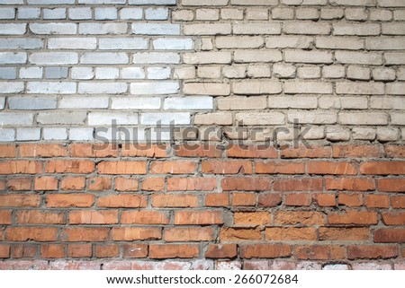 Grey and red brick wall background. Old bricks are replaced by new ones