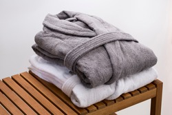 grey and white bath robes on wooden bench