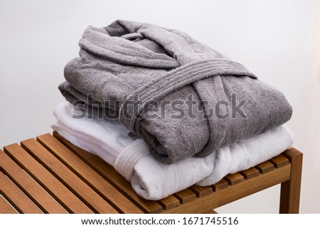 grey and white bath robes on wooden bench Stock foto ©