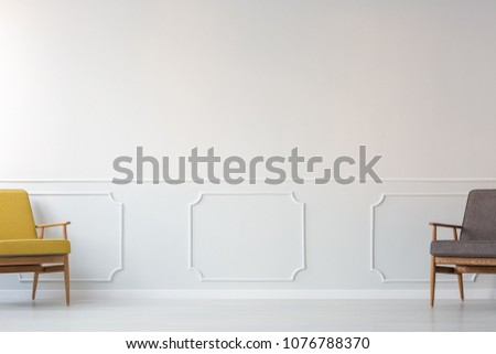Grey and yellow armchair in empty living room interior with copy space on white molding wall