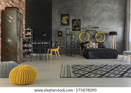 Grey apartment with bed, desk, chair, brick wall, yellow details - Shutterstock ID 575878090