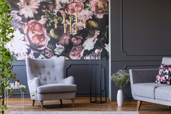 Grey armchair against flowers wallpaper in dark living room interior with sofa and plant. Real photo
