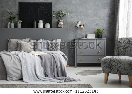 Grey armchair near cabinet and bed with sheets in bedroom interior with black poster. Real photo #1112523143
