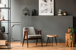 Grey armchair next to a wooden table in living room interior with plant and poster
