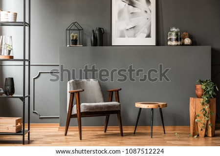 Grey armchair next to a wooden table in living room interior with plant and poster #1087512224