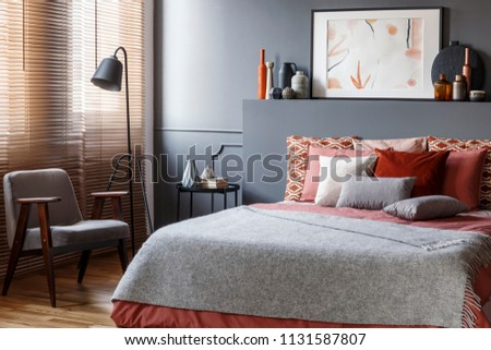 Grey armchair next to lamp in bedroom interior with poster on headboard of bed #1131587807
