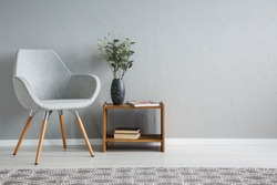 Grey armchair next to wooden table with flowers in flat interior with copy space on the wall. Real photo