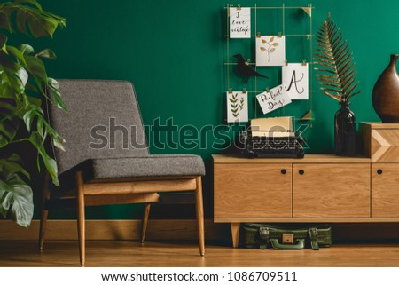 Grey armchair, wooden cupboard, typewriter and metal wall organizer in green living room interior #1086709511