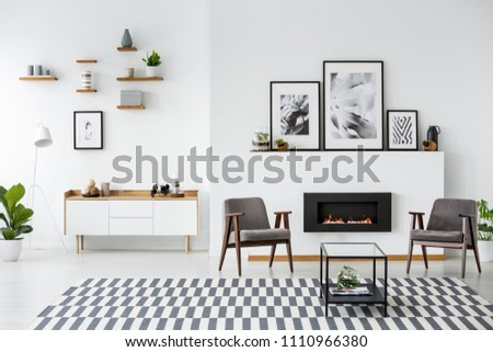 Grey armchairs between black fireplace in spacious apartment interior with posters. Real photo