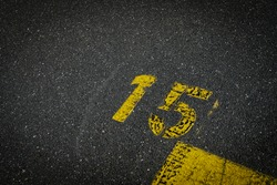 Grey asphalt road, yellow painted number fifteen on grey street, yellow lines like a corner on the road, space for text