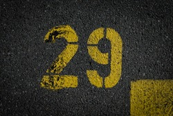 Grey asphalt road, yellow painted number twenty nine on grey street, yellow lines like a corner on the road, space for text