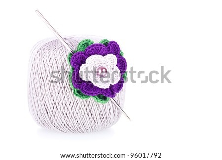 Grey ball of cotton knitting yarn with crochet and knitted flower on the white background