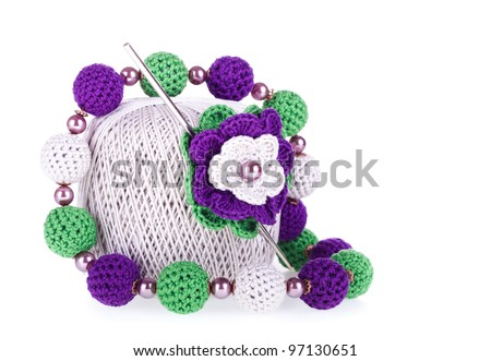 Grey ball of cotton knitting yarn with knitted flower, crochet and necklace on the white background