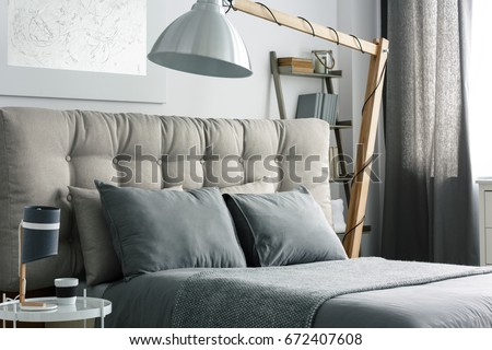 Grey bed with quilted headboard and big wooden lamp #672407608