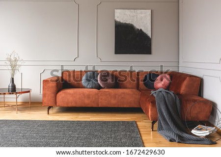 Grey, black, beige and pink round velvet pillows on ginger colored living room sofa