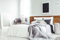 Grey blanket on bed with wooden bedhead in simple bedroom interior with dark poster and chair under window