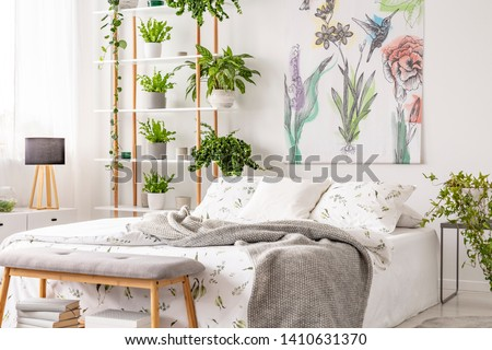 Grey blanket thrown on double bed with floral bedclothes standing in white room interior with painting, many fresh plants on wooden rack in the real photo #1410631370
