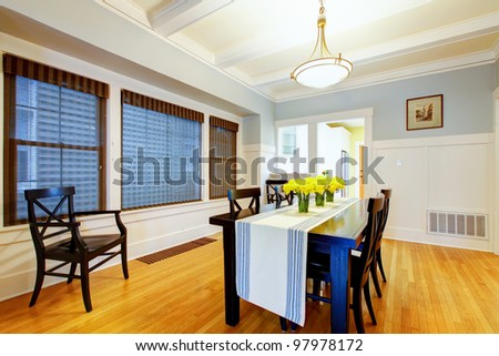 Grey blue dining room interior with black table and wood floor.