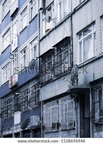 Grey blue residential house facades in traditional Jewish quarter Balal in Istanbul, Turkey with Turkish flag and TV antennas