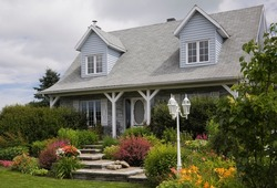Grey brick with white trim cottage style Canadiana home facade with landscaped front yard in summer