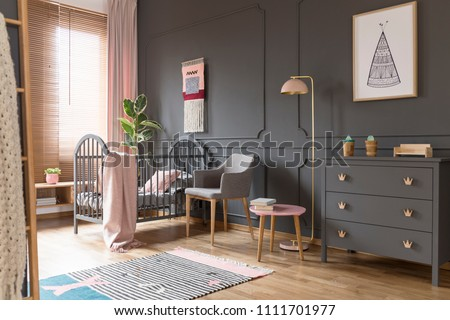 Grey cabinet next to pink lamp in simple baby's bedroom interior with blanket on bed. Real photo