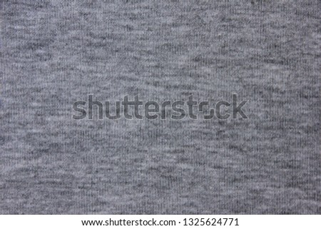 Grey canvas linen fabric texture background of simple shirt. Gray cloth pattern surface, casual material design, close up top view with empty seamless copy space on classic grey backdrop