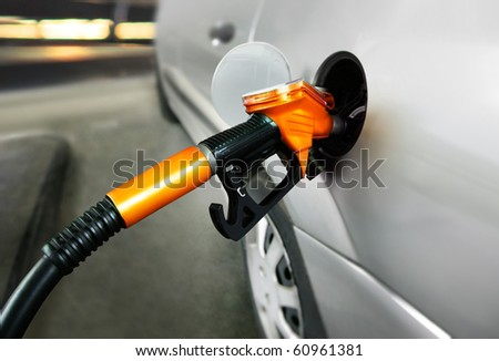 grey car at gas station being filled with fuel - stock photo