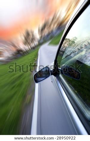 Grey car speeds through a country lane