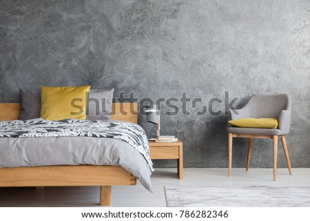 Grey chair and lamp on wooden nightstand in dark bedroom with concrete wall and yellow pillow on bed